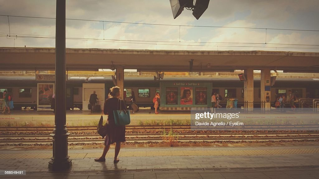 Rear View Of Woman Standing At Railroad Station Platform : Stock Photo