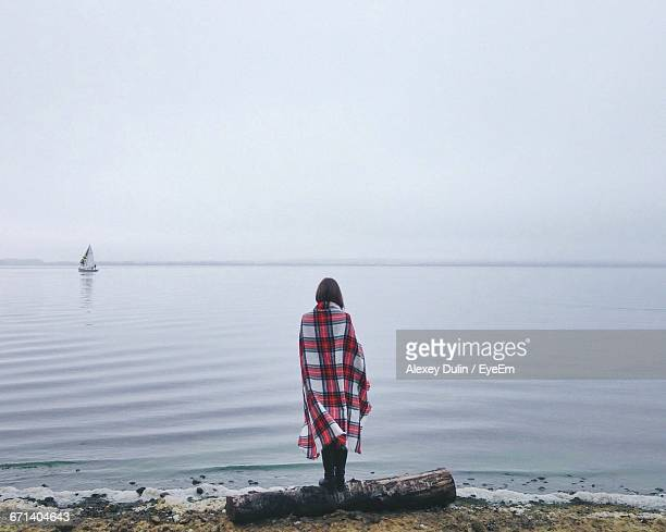 Rear View Of Woman Standing At Sea Shore During Foggy Weather