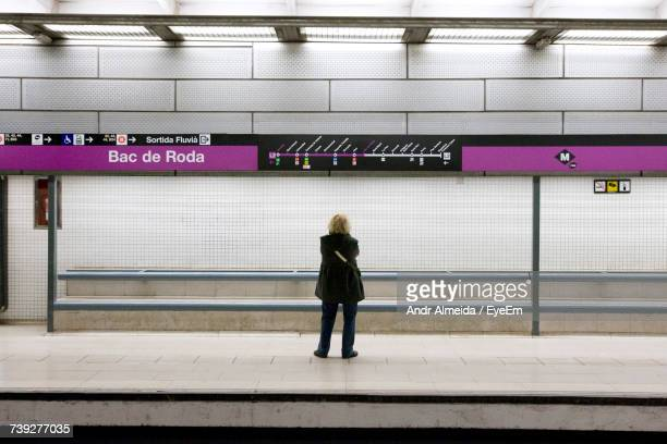rear view of woman standing at subway station - estação imagens e fotografias de stock