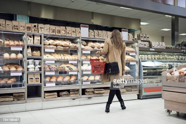 Rear view of woman standing by breads in rack at supermarket