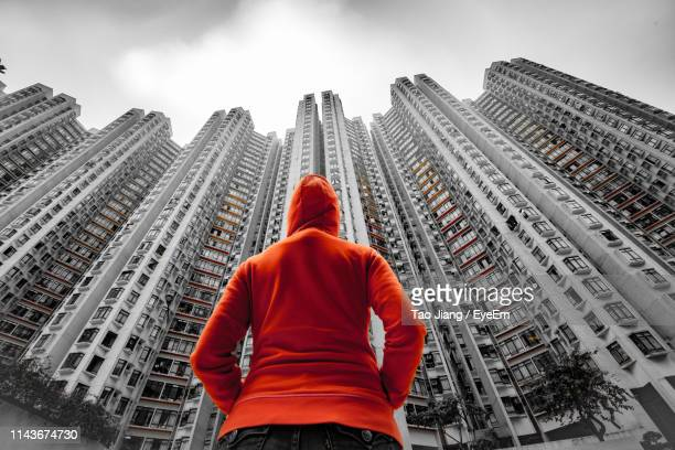 rear view of woman standing by buildings in city - isolated color stock pictures, royalty-free photos & images
