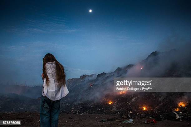 Rear View Of Woman Standing By Burning Garbage At Junkyard Against Sky