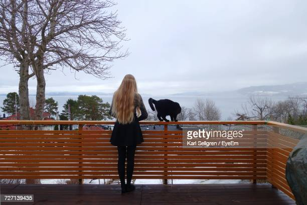 Rear View Of Woman Standing By Cat On Railing