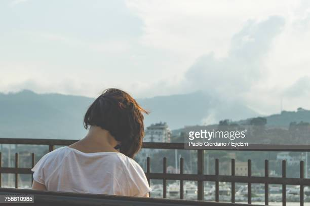 rear view of woman standing by fence against cloudy sky - one young woman only stock pictures, royalty-free photos & images