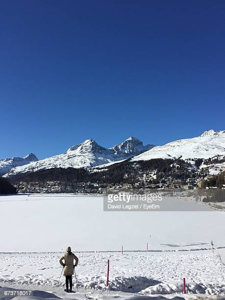 Rear View Of Woman Standing By Frozen Lake At Swiss Alps Against Clear Blue Sky