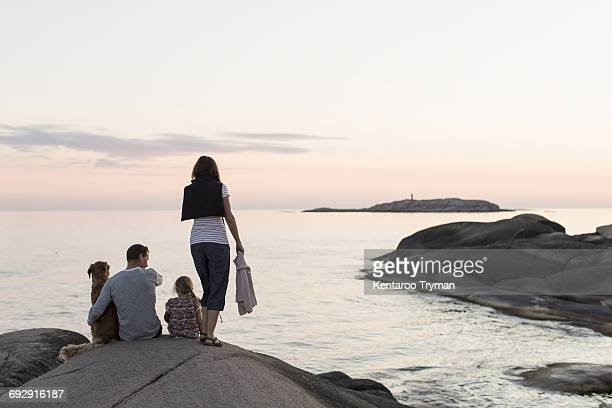 Rear view of woman standing by girl sitting with father and dog on rock formation against sky