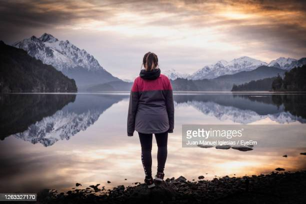 rear view of woman standing by lake against sky during sunset - bariloche stock pictures, royalty-free photos & images