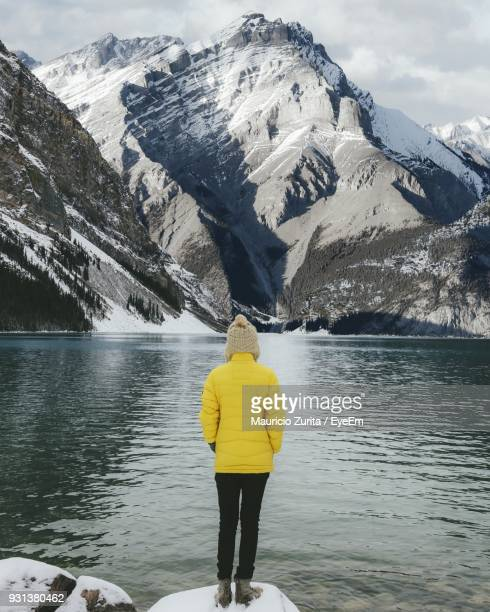 Rear View Of Woman Standing By Lake Against Snowcapped Mountain