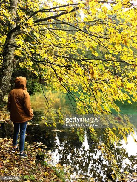 Rear View Of Woman Standing By Lake During Autumn
