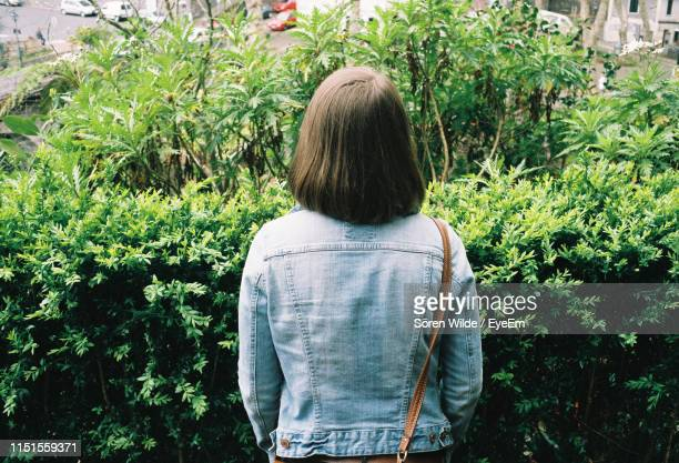 rear view of woman standing by plants in public park - denim jacket stock pictures, royalty-free photos & images