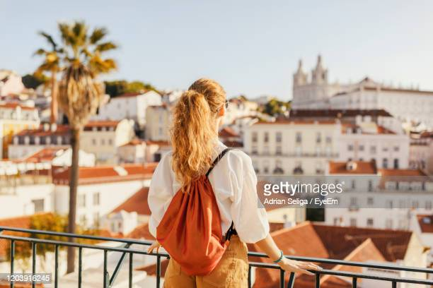 rear view of woman standing by railing against buildings and sky - lissabon stock-fotos und bilder