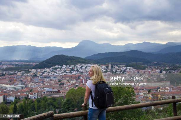 rear view of woman standing by railing against cloudy sky - catalonië stockfoto's en -beelden