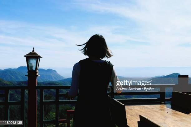 rear view of woman standing by railing against mountains and sky - anuwat somhan stock photos and pictures