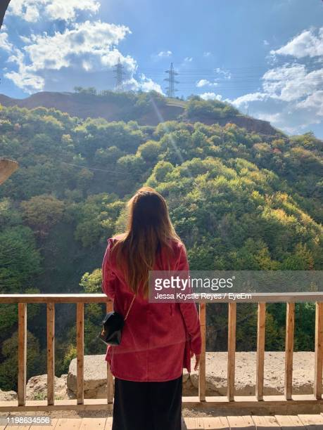 rear view of woman standing by railing against sky - jessa stock pictures, royalty-free photos & images