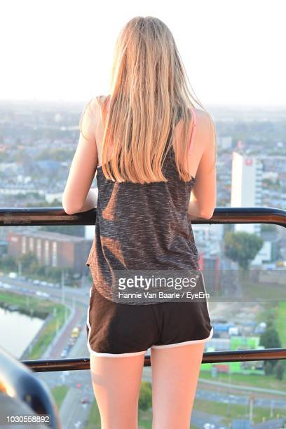 Rear View Of Woman Standing By Railing In Balcony