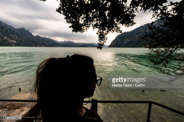 rear view of woman standing by railing over sea against sky - one young woman only stock pictures, royalty-free photos & images
