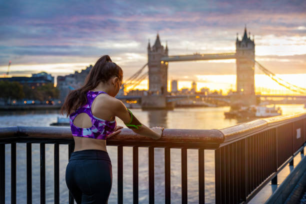 Rear View Of Woman Standing By Railing With London Bridge In Background Against Sky During Sunset