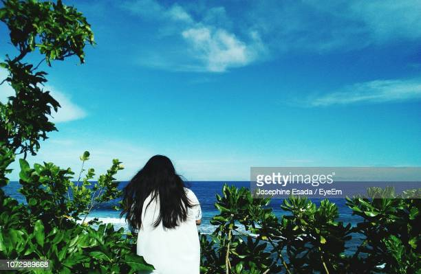 Rear View Of Woman Standing By Sea Against Blue Sky