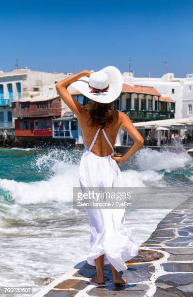 rear view of woman standing by sea against clear sky - sundress stock pictures, royalty-free photos & images