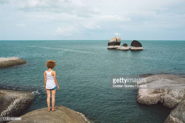 Rear View Of Woman Standing By Sea On Rock