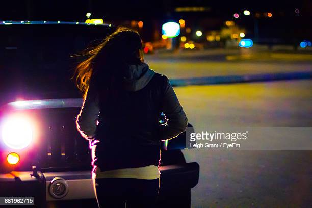rear view of woman standing by sports utility vehicle on street during night - leigh grant stock pictures, royalty-free photos & images