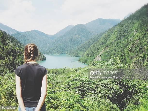 Rear View Of Woman Standing By Trees Against Mountains