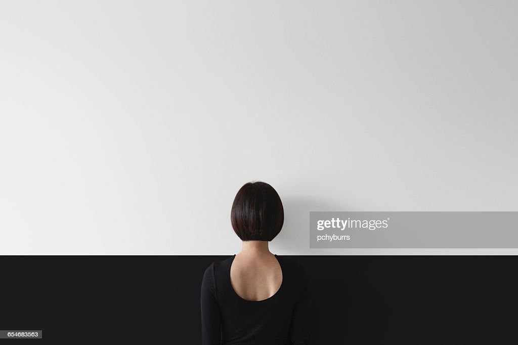 Rear view of woman standing facing wall : Stock Photo