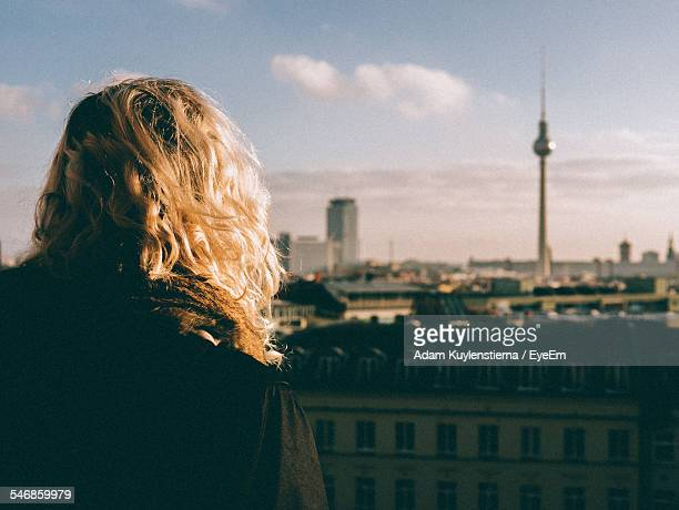 Rear View Of Woman Standing In Front Of Fernsehturm Tower