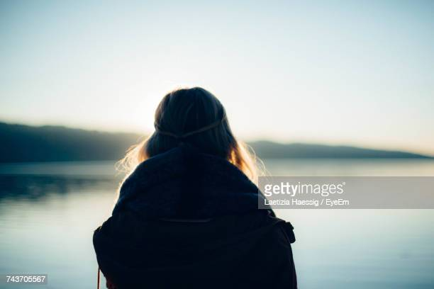 Rear View Of Woman Standing In Front Of Lake Against Sky