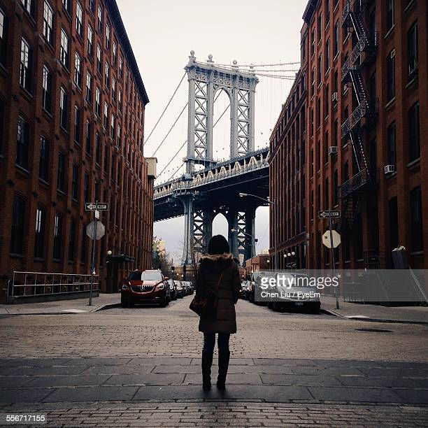 rear view of woman standing in front of manhattan bridge - brooklyn new york stock photos and pictures