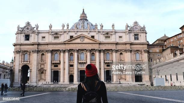 rear view of woman standing in front of st peters basilica - vatican city stock pictures, royalty-free photos & images