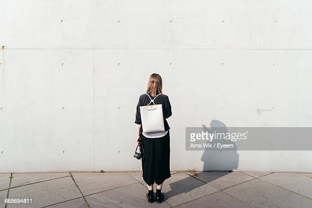rear view of woman standing in front of wall - in front of stock pictures, royalty-free photos & images