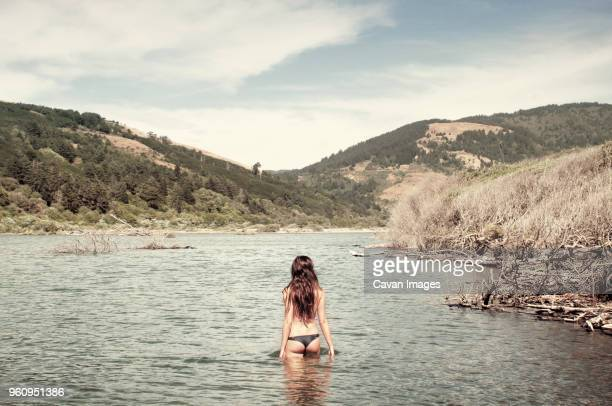 Rear view of woman standing in lake against mountains and sky
