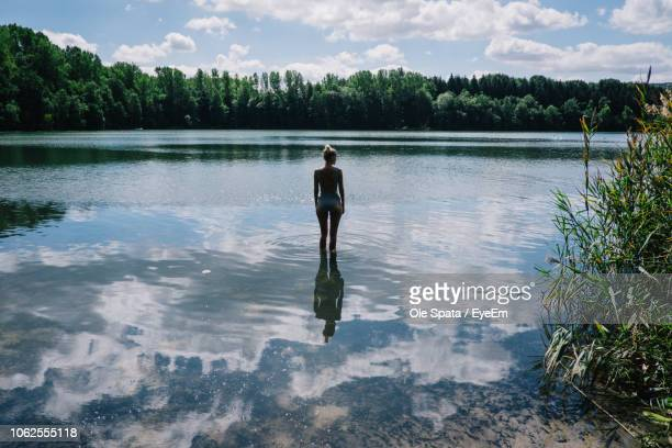 rear view of woman standing in lake with clouds reflection - ウォーターフロント ストックフォトと画像