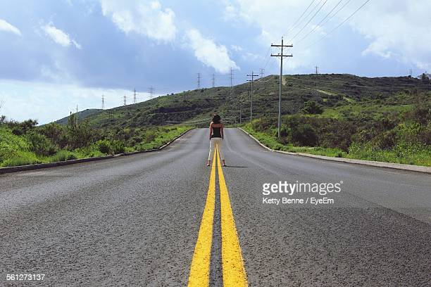 rear view of woman standing in middle of highway - benen gespreid stockfoto's en -beelden