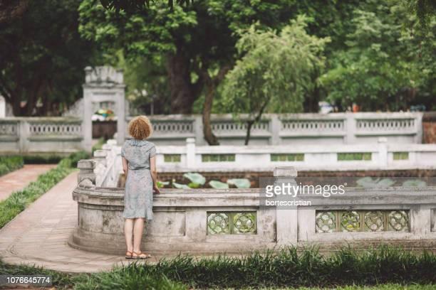 rear view of woman standing in park - bortes foto e immagini stock