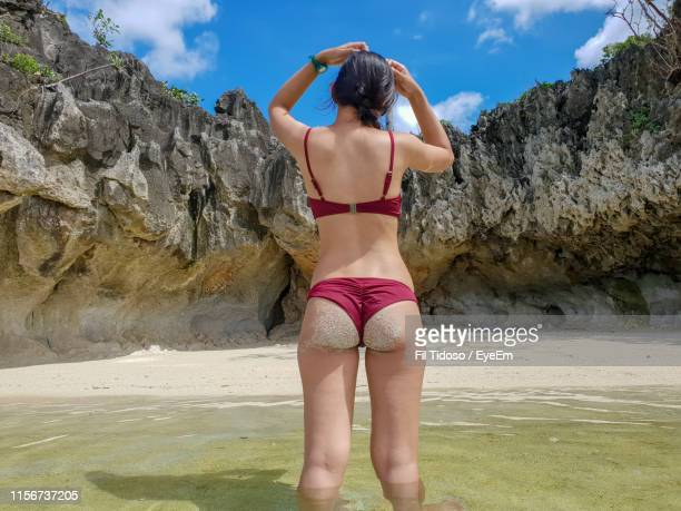 rear view of woman standing in sea against rock formation - monokini photos et images de collection
