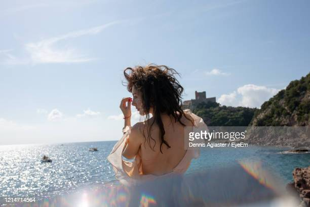 rear view of woman standing in sea against sky - backless stock pictures, royalty-free photos & images