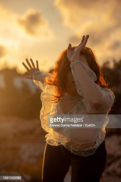 rear view of woman standing in water during sunset - lorena day stock pictures, royalty-free photos & images