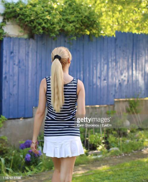 Rear View Of Woman Standing In Yard