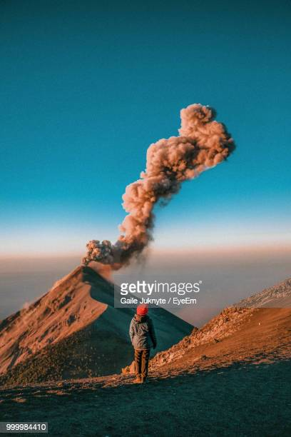Rear View Of Woman Standing Near Active Volcano