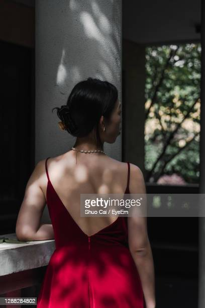 rear view of woman standing next to railing in shades - strapless evening gown stock pictures, royalty-free photos & images