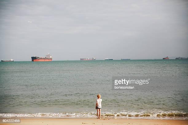 rear view of woman standing on beach against sea - bortes stock-fotos und bilder