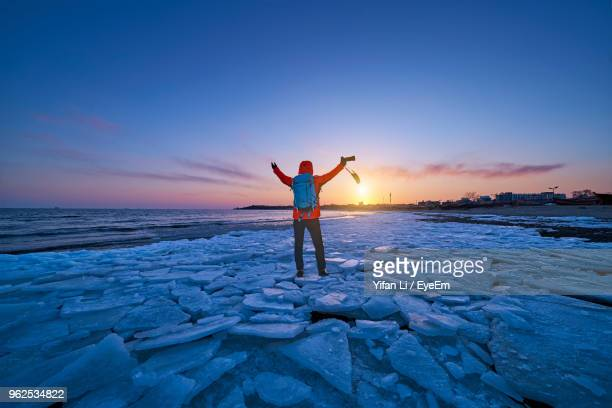 Rear View Of Woman Standing On Beach Against Sky During Sunset
