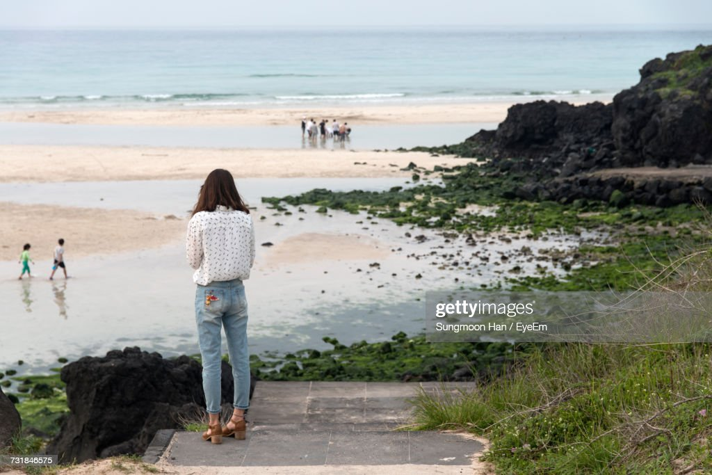 Rear View Of Woman Standing On Beach Against Sky : Stock Photo