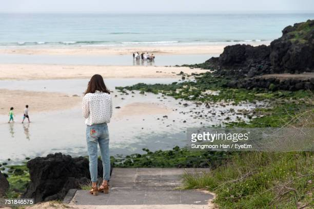 rear view of woman standing on beach against sky - jeju stock photos and pictures