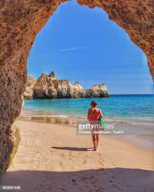 rear view of woman standing on beach against sky - alvor stock pictures, royalty-free photos & images