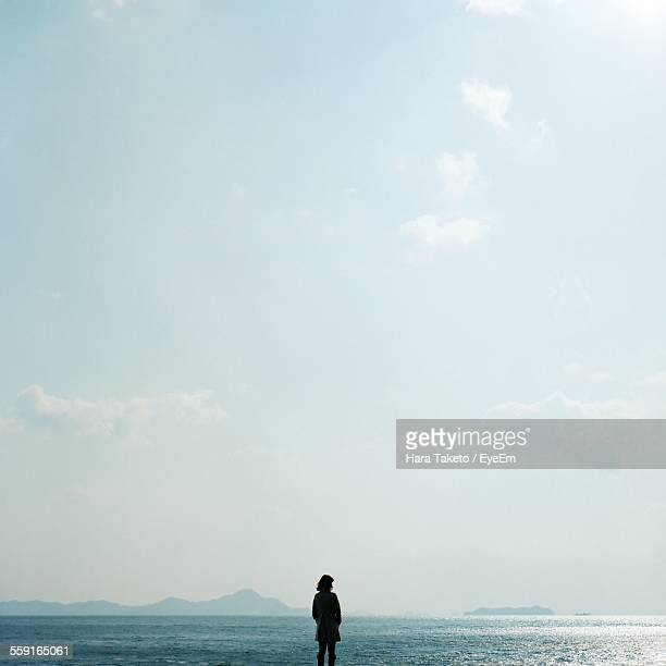 rear view of woman standing on beach - horizon over water stock pictures, royalty-free photos & images