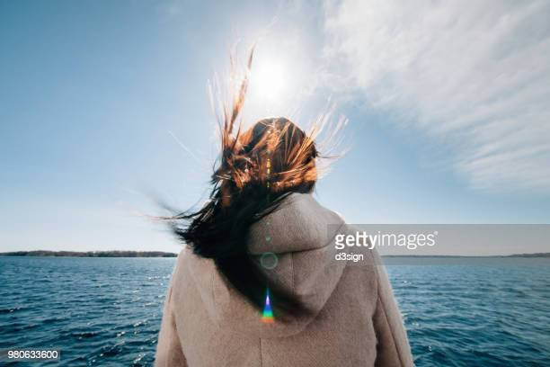 Rear view of woman standing on boat enjoying sea breeze and admiring ocean
