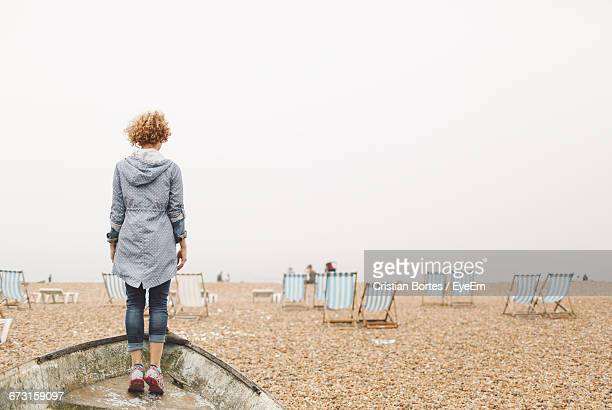 Rear View Of Woman Standing On Boat Moored At Beach Against Clear Sky